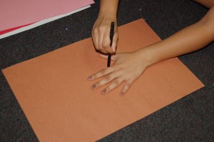 1.Cut tree trunk out of brown paper by tracing your hand.