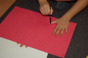 3. Trace hand onto construction paper.