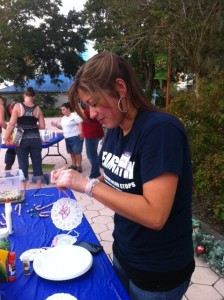 Jacklyne Ramos makes snowflake ornaments at the Winter Wonderland craft station with the children and their families.